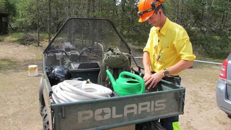 En man i gul skjorta och orange hjälm står vid en sexhjulig motorcykel som innehåller utrustning.