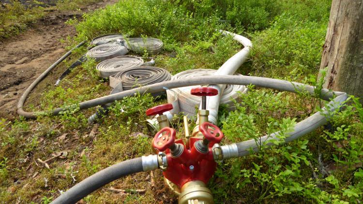 Slangkoppling och vattenslangar som ligger på marken.