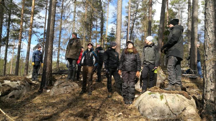 En grupp människor står i skogsgläanta och försöker försöker få sol i ansiktet.