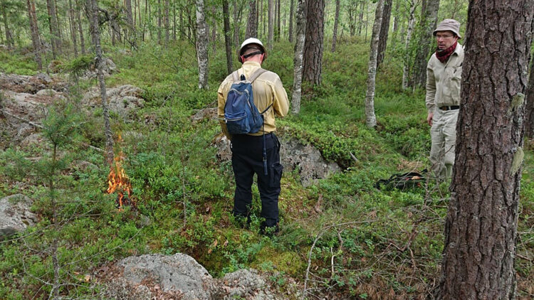 En man med svartabyxor, gul skjorta och blå ryggsäck står bredvid en liten eld.