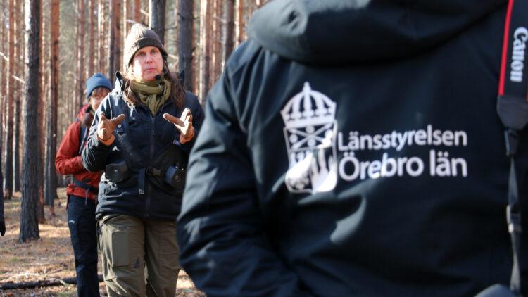 En kvinna i friluftskläder pratar. Närmast i bild en jacka med trycket Länsstyrelsen i Örebro län.