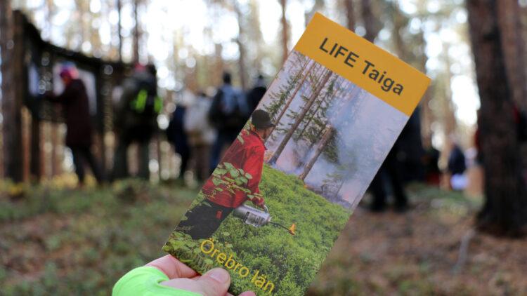 En folder hålls upp framför kameran. I bakgrunden står en grupp männinskor på en lite höjd vid en skyllt.