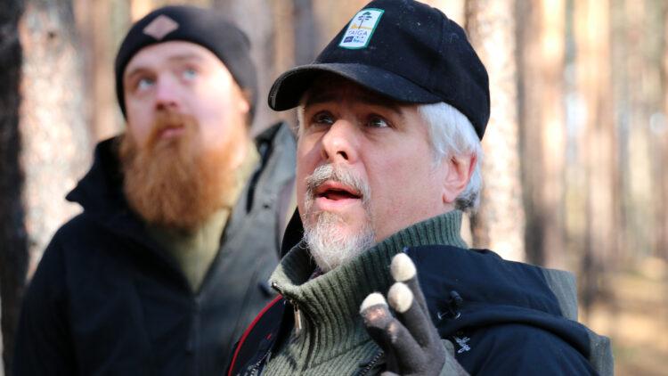 En man i svart keps och skägg pratar.