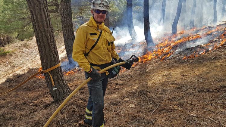 En man med gul skjorta och vit hjälp håller i en brandslang. han står framför mark som brinner med låga lågor.