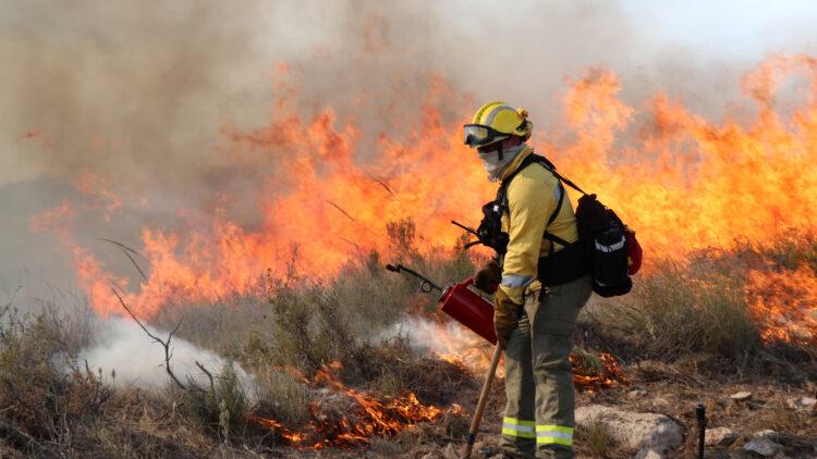 En person med gul skjorta och gul hjälm står framför flammande lågor. Hans ansikte är täckt. I ena handen håller personen en tändkanna, i andra en hacka.