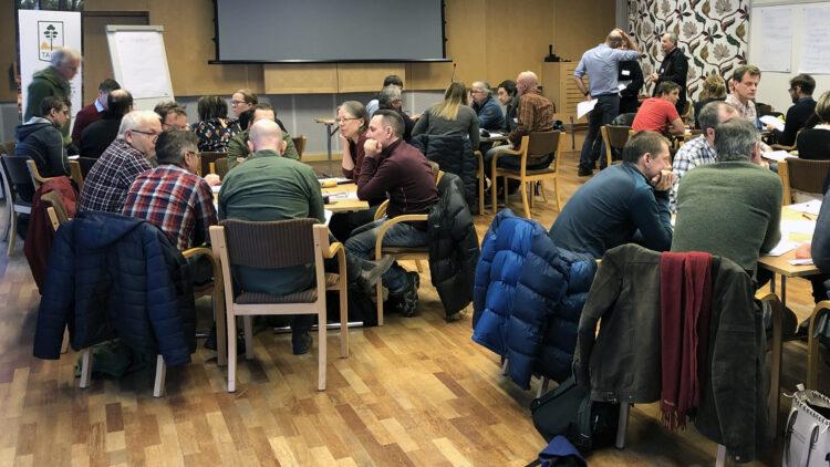 Enn 40-tal männinskor sitter runt sex bord och samtalar.