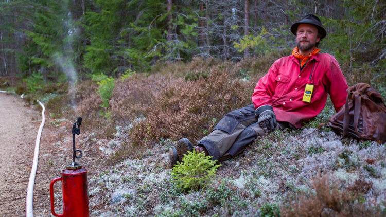 En man i rödskjorta, hatt och skägg sitter i vitmossa. Bredvid mannen en liten bit ifrån står en eldkanna på en skogsväg.