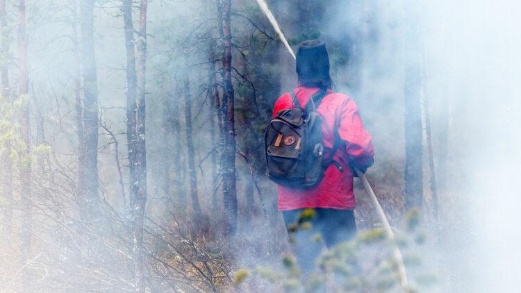 En person i röd skjorta och ryggsäck syns genom rök. Personen håller en vattenslag och sprutar vatten.