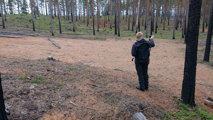 Ryggtavlan på en svartklädd man med blont hår som håller upp en kamera. mannen står vis en stor sandig ytan kantas av sotiga tallstammar.